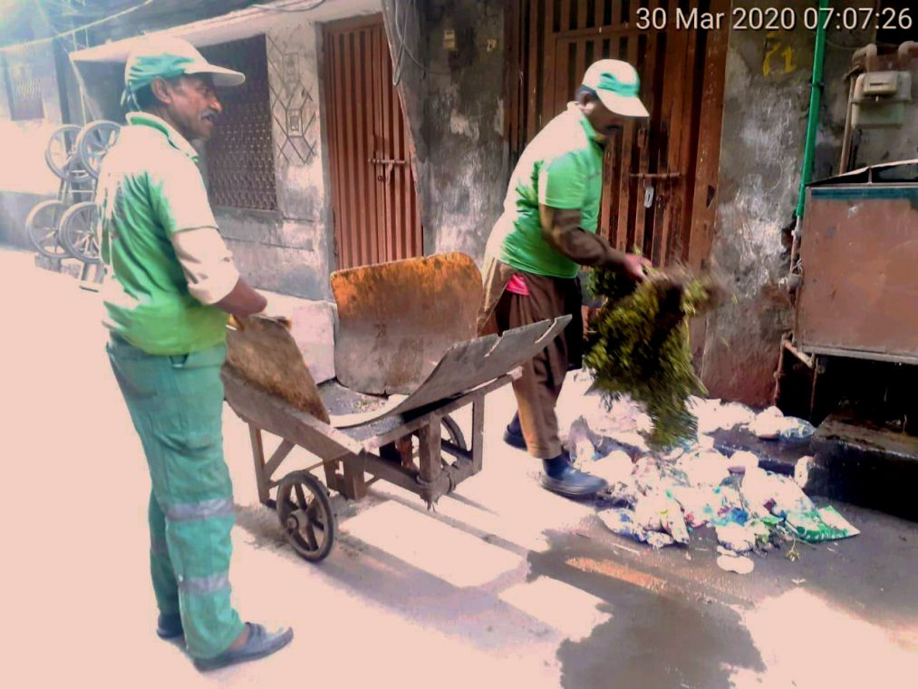 scooping up the garbage without gloves or masks
